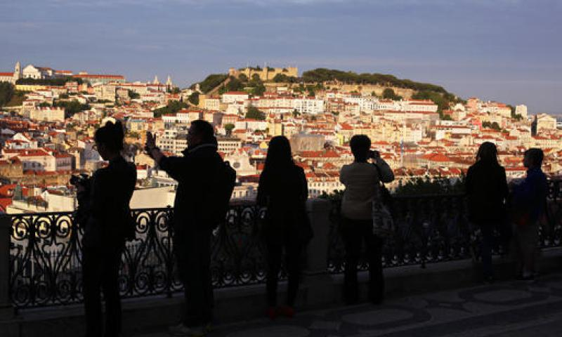 In this May 25, 2016 photo, tourists taking pictures are silhouetted against Lisbon's old center lit by the setting sun. With sunny days getting longer and lazier, sparkling beaches warming up and terrorism fears driving customers away from other Mediterranean destinations, Spain and Portugal are reaping an economic bonanza from tourism.  Armando Franca/AP