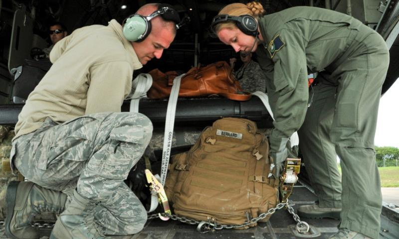 U.S. Air Force Tech. Sgt. Chad Burk, left, crew chief from the 435th Aircraft Maintenance Squadron, Ramstein Air Base, Germany, and Nevada Air National Guard Senior Airman Alanna Vick, C-130 Hercules aircraft loadmaster from the Reno-based 192nd Airlift Squadron, work together to release passenger luggage for soldiers and airmen taking part in the 70th commemoration of D-Day at Cherbourg-Maupertus Airfield, France, on June 2, 2014, in support of Allied Forge 2014.  Erica J. Knight/USAF