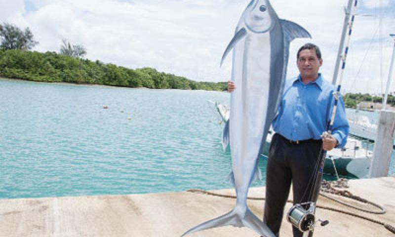 Peter Perez  re-enacts a pose after catching a winning marlin at the Sumay Cove Marina on U.S. Naval Base Guam Aug. 31. Though Perez manages equipment on land, his passion has fins and is found under the sea. U.S. Navy photo by Shaina Marie Santos/Released