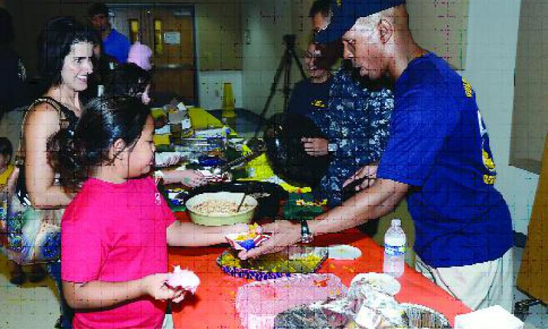 Sailors from USS Frank Cable (AS 40) serve different types of Spanish food to Cmdr. William C. McCool Elementary and Middle (MEMS) school students during a Hispanic Heritage Month Fair at the school on U.S. Naval Base Guam Oct. 12. The fair was the school's final event in celebration of Hispanic Heritage Month. U.S. Navy photo by Mass Communication Specialist 2nd Class Jeremy Starr