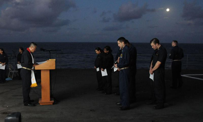 PHILIPPINE SEA (April 5, 2015) Lt. Cmdr. Louis Lee, left, command chaplain for the submarine tender USS Frank Cable (AS 40), hosts an Easter Sunday sunrise service on the flight deck. Frank Cable, forward deployed to the island of Guam, conducts maintenance and support of submarines and surface vessels in the U.S. 7th Fleet area of responsibility and is currently on a scheduled underway period. (U.S. Navy photo by Mass Communication Specialist 1st Class Brandon Shelander)