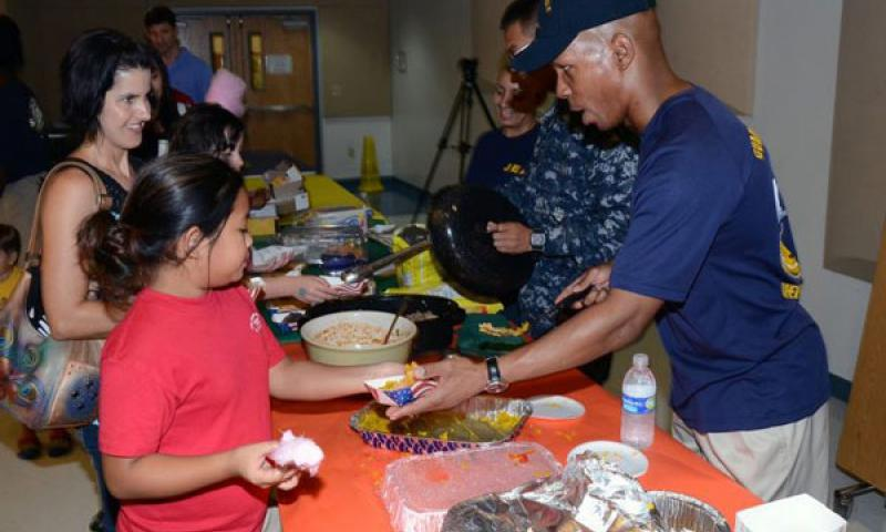 Sailors from USS Frank Cable (AS 40) serve different types of Spanish food to Cmdr. William C. McCool Elementary and Middle (MEMS) school students during a Hispanic Heritage Month Fair at the school on U.S. Naval Base Guam Oct. 12. The fair was the school's final event in celebration of Hispanic Heritage Month. (U.S. Navy photo by Mass Communication Specialist 2nd Class Jeremy Starr)
