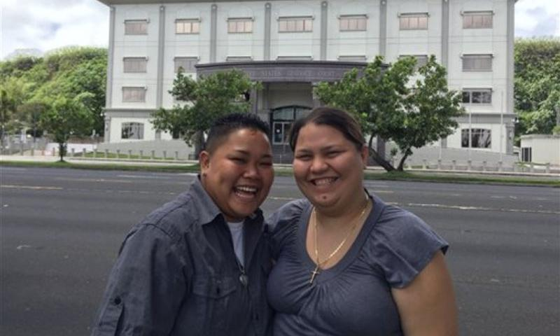 Lesbian couple Loretta M. Pangelinan, left, and Kathleen M. Aguero have their picture taken in front of the U.S. District Court in Hagatna, Guam, April 11, 2015. The couple had challenged the territory's marriage laws with a lawsuit.  Grace Garces Bordallo/AP
