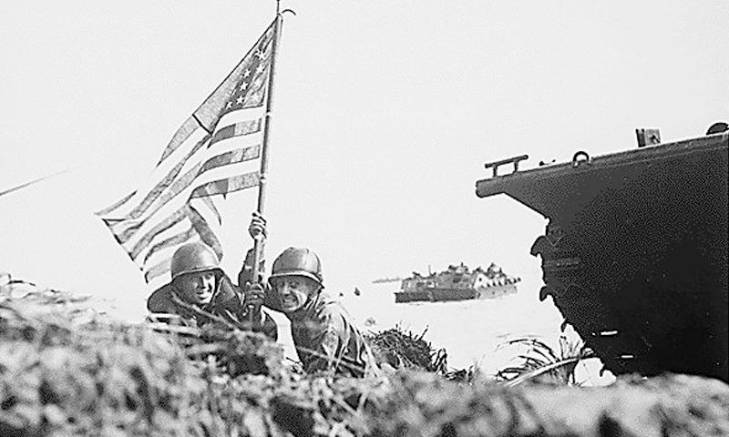 Two U.S. Marines (on the left is Captain Paul S. O'Neal of Brighton Mass., and on the right is Captain Milton F. Thompson of Upper Montclair N.J.) plant the American flag on Guam eight minutes after U.S. Marines and Army assault troops landed.