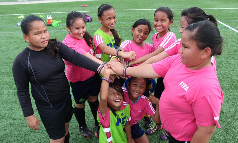 "Coach Walter Benavente's U10 team in the GFA & The Score's ""Just Kick It 2"" All-Girls Event pose for a photo with their gift bracelets from their coach. From left to right, standing, are Daneeka Ungacta, Gabby Manansala, Melanie Damian, Jodee Rose Halili, Kaylee Duenas, Jadyn Palomares (partially hidden) and Dominique Ungacta. Kneeling, in front, are from left, Sarah Benavente and Jada Han."