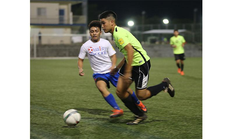 Bank of Guam Strykers' Joshua Calvo makes a run past Quality Distributors' Melvin Cristobal in the opening U18 division match of the Aloha Maid Minetgot Cup Elite Youth League at the Guam Football Association National Training Center Monday evening. The Strykers won 5-0.