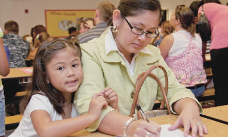 Army spouse Lynnette Cepeda Cruz fills out a form to schedule a home visit with her child's teacher at the Cmdr. William C. McCool Elementary and Middle School kindergarten orientation on U.S. Naval Base Guam Aug. 24.