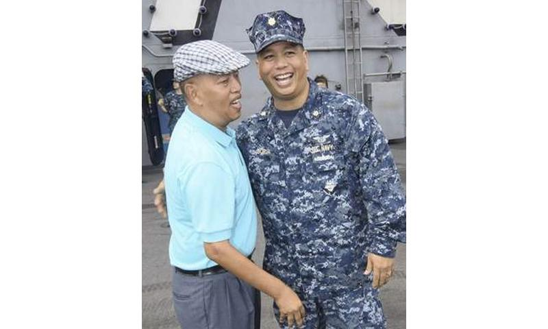 Retired Navy Cmdr. Joe Borja of Santa Rita, left, is reunited with his brother, Lt. Cmdr. Ivan Borja, aboard the USS George Washington shortly after the aircraft carrier's arrival to Naval Base Guam on Oct. 2. The carrier arrived for a port call after taking part in exercise Valiant Shield 2014 in the waters near Guam.  Mark Scott/Pacific Daily News