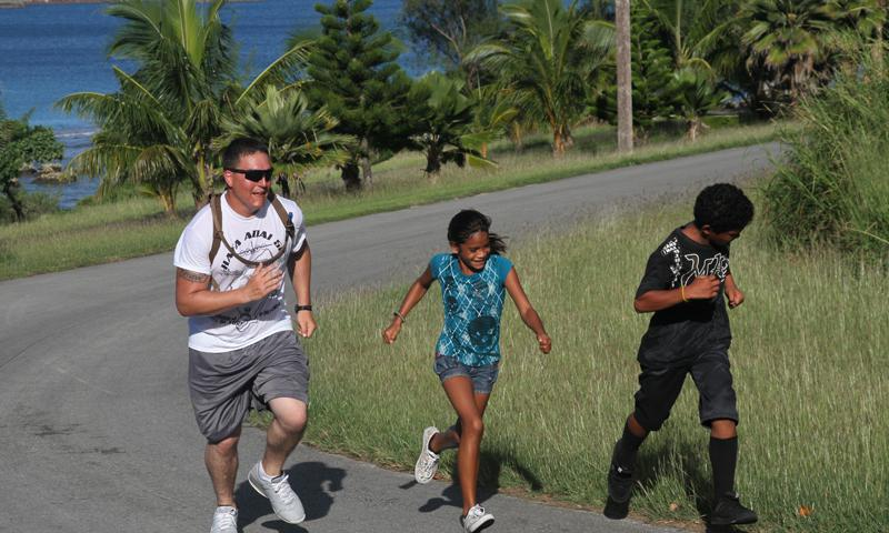 Cpl. Mark Montoya runs alongside two local participants of the Tinian Hafa Adai 5K Fun Run here Dec. 8 during Exercise Forager Fury 2012. The Marines and local Tinian Police Department coordinated the fun run which included local participants of all ages. Montoya is an electrician Marine Wing Support Squadron 171, Marine Aircraft Group 12, 1st Marine Aircraft Wing, III Marine Expeditionary Force. (U.S. Marine Corps photo by Lance Cpl. J. Gage Karwick)