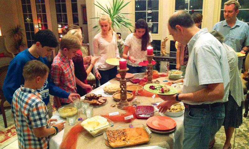 Theresa Starta and her family host guests from other countries at their home in Dubai, serving a traditional turkey dinner on Thanksgiving and sharing the history of each dish. Spending the holiday season far from home can be challenging for American families living overseas. One solution: Invite friends in your host country over for a holiday meal, sharing your family's traditions with people who may never have learned about them before. Photo by Christina Lundgren, AP
