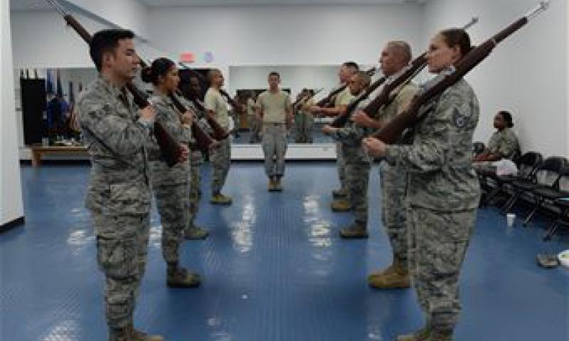 Senior Airman Patrick Duffie, a ceremonial guardsman from the 36th Operations Support Squadron, center, shouts commands while Andersen Blue Knights Honor Guard members practice weapons movements with training rifles June 24, 2015, at Andersen Air Force Base, Guam. Honor guard members follow strict guidelines while performing their duties to provide traditional military honors at ceremonies and funerals. (U.S. Air Force photo by Senior Airman Amanda Morris)