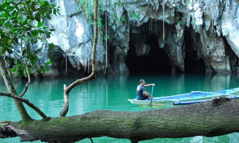 A guide paddles by the mouth of the underground river during a tour of the Puerto Princesa Subterranean River National Park in the Philippines.