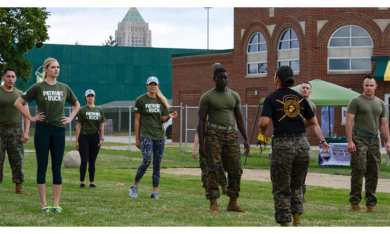 Kate Upton and others listen to instructions from GySgt. Sara Pacheco before they executed a workout at Wayne State University's athletic complex in Detroit on Aug. 22, 2017. Upton and others completed a circuit course consisting of several rounds of burpees, sprints, jumping jacks and more in an effort to promote Marine Week Detroit that takes place Sept. 6-10.
