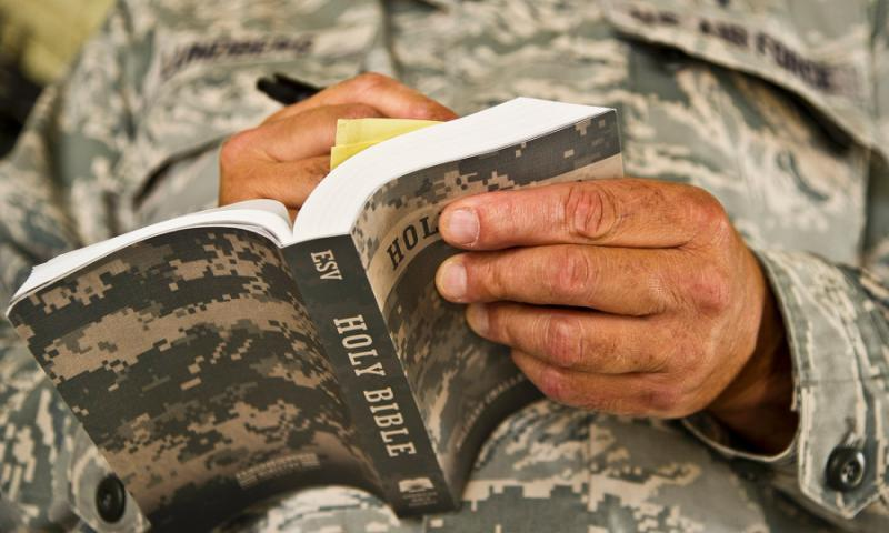 "An Air Force chaplain reads from his Bible during a training scenario on Aug. 19, 2017. Air Force Capt. Sonny Hernandez, a chaplain with the 445th Airlift Wing at Wright-Patterson Air Force Base in Ohio, is under fire for saying that Christian servicemembers should not support the rights of other religions to practice their faith, saying ""that will lead them to hell."" EFREN LOPEZ/U.S. AIR FORCE"
