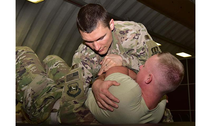 Capt. Eric Walter, 386th Expeditionary Medical Group physical therapy element chief, uses thoracic manipulation to treat Senior Airman Calvin Lourens, 386th Expeditionary Logistics Readiness Squadron passenger service specialist, Dec. 7, 2017, at an undisclosed location in Southwest Asia. (U.S. Air Force photo by Tech. Sgt. Louis Vega Jr.)