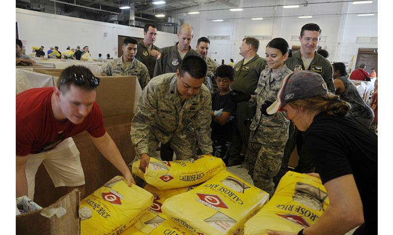 Air Force Lt. Col. Melvin Ibaretta, the deputy commander of the Air Force Reserve's 624th Regional Support Group, works with members of the 44th Aerial Port Squadron by grabbing a bag of rice to include in a Christmas bundle during Operation Christmas Drop at Andersen Air Force Base, Guam, Dec. 9, 2017. Operation Christmas Drop has been providing critical supplies to 56 Micronesian Islands since 1952. Air Force photo by Master Sgt. Theanne Herrmann