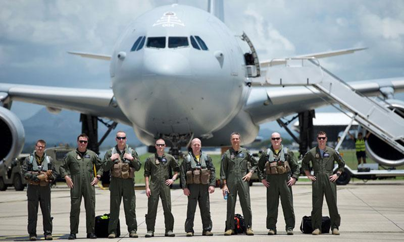 A U.S. Air Force B 1B Lancer crew with the 37th Expeditionary Bomb Squadron, stand for a group photo alongside a Royal Australian Air Force aircrew with the No. 33 Squadron, after conducting a first of its kind aerial refuel at RAAF Base Amberley, Australia. Two bombers arrived at Amberley as part of the United States-Australia Force Posture Initiatives En- hanced Air Cooperation program, which builds on air exercises and training between the two air forces. (Photo by Master Sgt. Farrah S.C. Kaufmann/Releas