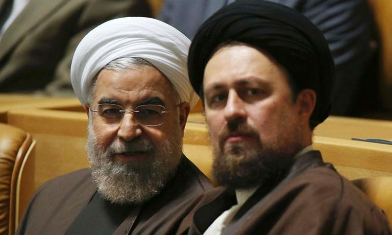 Iranian President Hassan Rouhani, left, talks to Hassan Khomeini, grandson of late revolutionary founder Ayatollah Khomeini, in a ceremony to commemorate the late Khadijeh Saghafi, wife of Ayatollah Khomeini, in Tehran, Iran, Sunday, April 12, 2015. VAHID SALEMI/AP