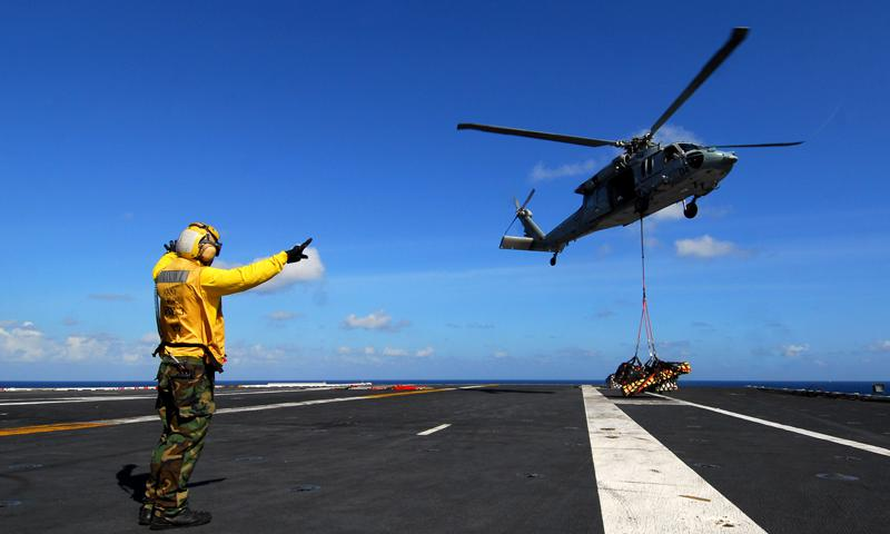 Petty Officer 3rd Class John Keith Elopre, aviation boatswain's mate (handling), from Fontana, Calif., directs an MH-60S Sea Hawk helicopter from the Island Knights of Helicopter Combat Support Squadron 25 during a replenishment at sea aboard the nuclear-powered aircraft carrier USS George Washington. George Washington is underway in the U.S. 7th Fleet area of responsibility. Photo by Seaman Jacob D. Moore