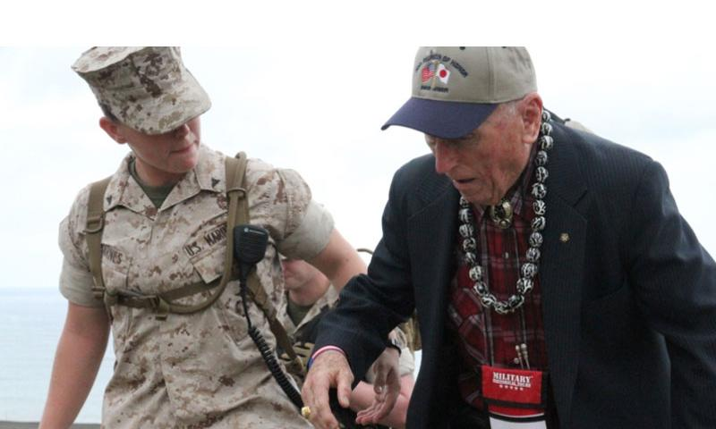 Marine Lance Cpl. Morgan Barnes helps steady Battle of Iwo Jima veteran and fellow Marine Carl DeHaven as he makes his way to the ceremony commemorating the 70th anniversary of the World War II battle.  Matthew M. Burke/Stars and Stripes