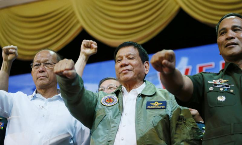 Philippine President Rodrigo Duterte, center, gestures with a fist bump, along with Defense Chief Delfin Lorenzana, left, and Armed Forces Chief Ricardo Visaya, during a talk to Philippine airmen on the anniversary of the 250th Presidential Airlift Wing, Tuesday, Sept. 13, 2016, at the air force headquarters in suburban Pasay city, southeast of Manila.  Bullit Marquez/AP