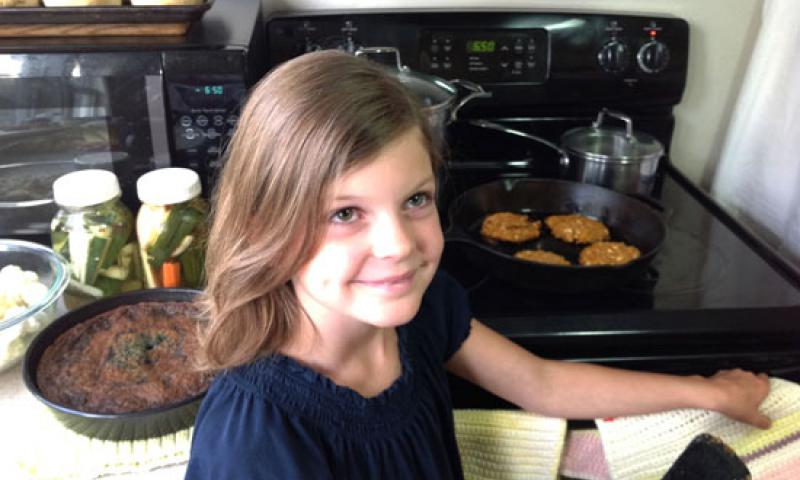 Finwe Wiendenhoeft, 9, cooks barbeque cheddar chickpea burgers in her southwest Wisconsin home. The recipe she developed with her mother won them seats at the first White House Kids' State Dinner, Aug. 20, 2012. Courtesy photo