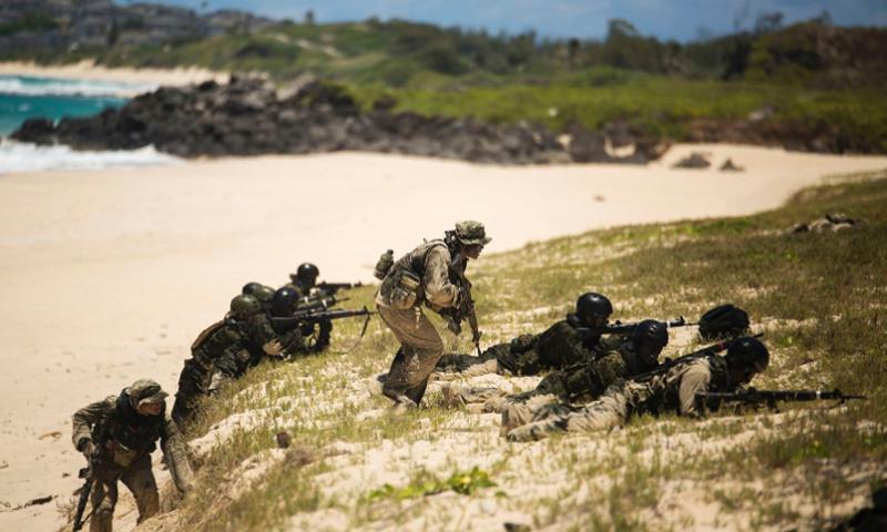 Two Japan Ground Self-Defense Force soldiers (left and center) advance to cover while their squads provide cover during an amphibious assault at Pyramid Rock Beach. The JGSDF conducted the training exercise with U.S. Marines with 3rd Reconnaissance Battalion, based in Okinawa, Japan.    Matthew J. Bragg/U.S. Marine Corps