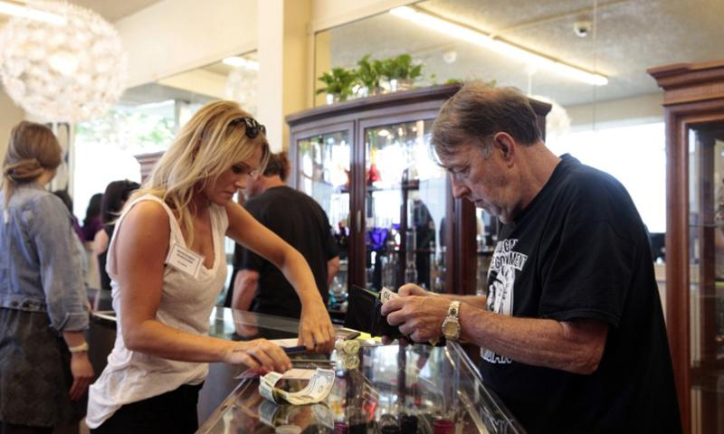 At Main Street Marijuana in Vancouver, Wash., a customer buys marijuana on the first day of sales at the store on July 9, 2014.  Beth Nakmura, The Oregonian/AP