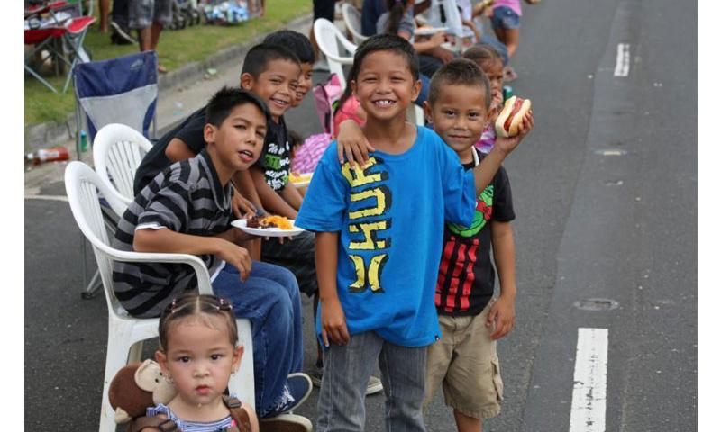 Local children smile as Soldiers from Task Force Talon, 94th Army Air and Missile Defense Command, march by during the 2015 Guam Liberation Day Parade. This was the first time TF Talon participated in Liberation Day activities since deploying to Guam over two years ago. (Photo by 1st Lt. Andrew Schumaker, Assistant Operations Officer, TF Talon, 94th AAMDC)