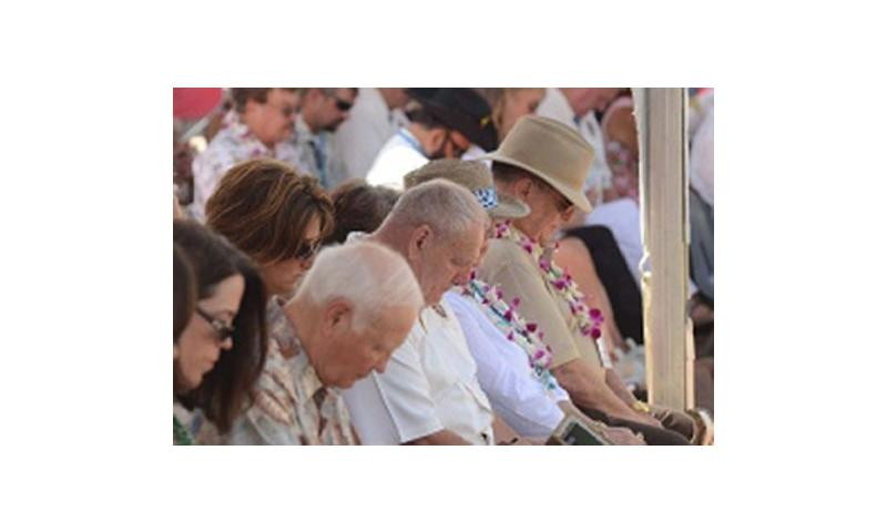 Medal of Honor recipient Kenneth Stumpf, center, bows his head in prayer along with other spectators at the National Cemetery of the Pacific in Honolulu on Oct. 3, 2012. Stumpf and 51 other Medal of Honor recipients -- more than anyone present could remember gathering in one place -- honored past medal recipients buried at the cemetery with a stone memorial dedication. Erik Slavin/Stars and Stripes