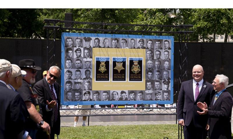 Jan C. Scruggs, founder and president of the Vietnam Veterans Memorial Fund, and several Medal of Honor recipients unveil the Limited Edition Medal of Honor: Vietnam War Forever Stamps at the annual Memorial Day Observance at the Vietnam Veterans Memorial, May 25, 2015. Rick Vasquez/Stars and Stripes