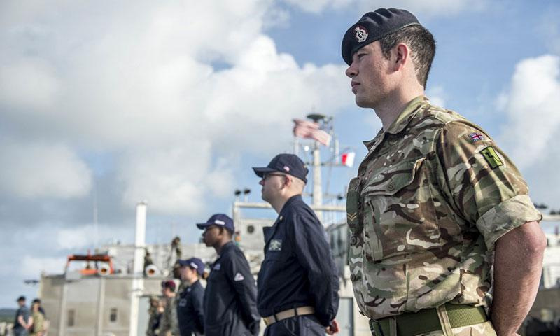 Combined forces aboard the expeditionary fast transport ship USNS Brunswick man the rails as the ship arrives in Colonia, Micronesia, for the first stop of Pacific Partnership 2018, March 20, 2018. Navy photo by Seaman Caledon Rabbipal