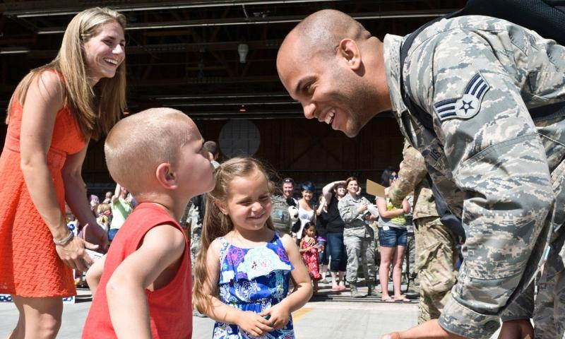 Senior Airman Decoltius Dickerson, 726th Air Control Squadron, returns from deployment to his wife and children at a celebration at the Mountain Home Air Base flightline, May 23, 2014, at the base in Southwestern Idaho. Kevin Wallace/U.S. Air Force