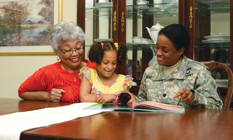 From right: Lt. Col. Lisa Whittaker, commander at 78th Signal Battalion, reads a book to her 7-year-old daughter Kyndall along with her mother, Belinda, at home on Camp Zama, Japan. Photo by Tetsuo Nakahara