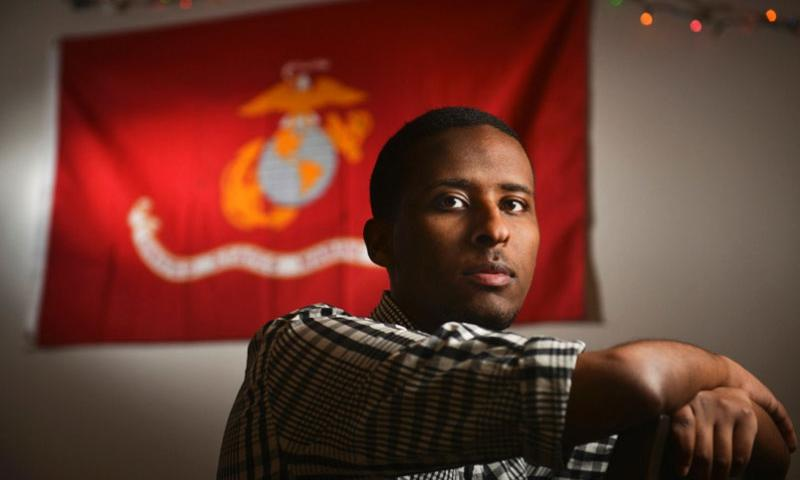 Ibrahim Hashi, a Muslim veteran of the United States military, is pictured in his American University dorm room, where a Marine Corps flag hangs on his living room wall. Since leaving the Marines as a corporal in 2011, Hashi has heard more anti-Muslim rhetoric than ever.   Jahi Chikwendiu/The Washington Post