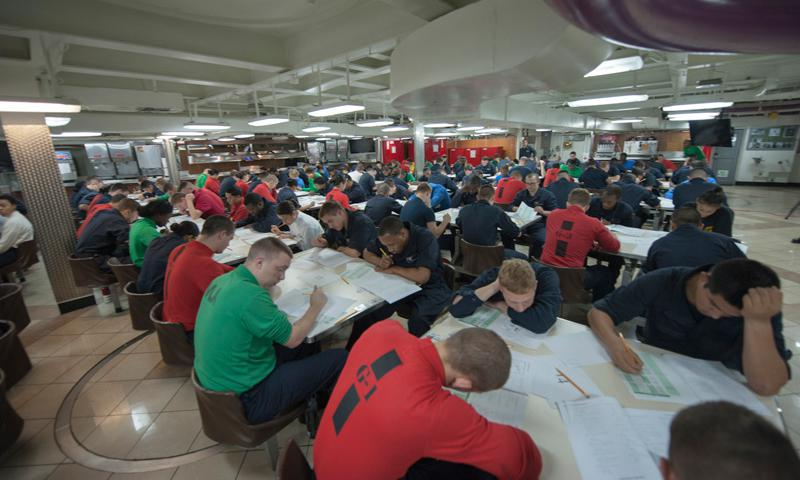 PACIFIC OCEAN (Sept. 18, 2014) Sailors take the Navy-wide petty officer 3rd class advancement exam on the mess decks aboard aircraft carrier USS Carl Vinson (CVN 70). Carl Vinson and its embarked air wing, Carrier Air Wing (CVW) 17, are on deployment in the U.S. 7th Fleet area of responsibility supporting Valiant Shield. Valiant Shield is a U.S.-only biennial exercise in which participation will focus on the integration of joint training among U.S. forces. (U.S. Navy photo by MC2 Scott Fenaroli)