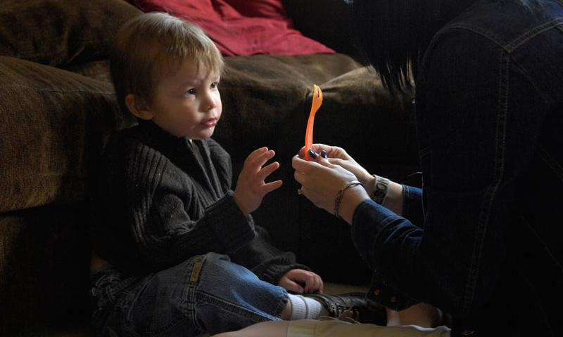 VIRGINIA BEACH (2010) Three-year-old Joey Adams reaches for a fork after correctly identifying the utensil to Board Certified Behavior Analyist therapist Kenna Nelson during an in-house therapy session. Joey Adams, diagnosed with severe Autism Spectrum Disorder is enrolled in the EFMP, a service-wide initiative designed to interface closely with the detailing process to ensure family members receive the care they require and service members can fulfill their career requirements and goals.