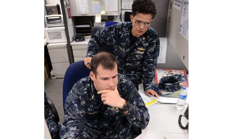 MILLINGTON, Tenn. (Dec. 12, 2012) Chief Warrant Officer Liz Rivera, combat systems rating assignment officer at Navy Personnel Command, trains Chief Firecontrolman Mike Zdunkawicz on how to use the Enlisted Assignment Information System (EAIS). Detailers use EAIS in conjunction with Career Management System/Interactive Detailing to post Sailors to billets. (U.S. Navy photo by Mass Communication Specialist 2nd Class Andrea Perez)
