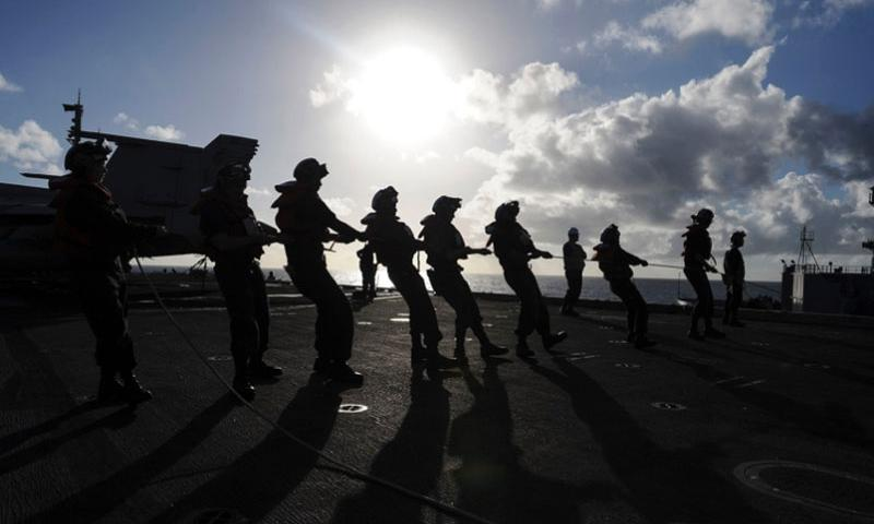 Sailors from Deck department hold the phone and distance line on the flight deck of the aircraft carrier USS Theodore Roosevelt while alongside the Military Sealift Command dry cargo and ammunition ship USNS Matthew Perry for a replenishment at sea on Nov. 9, 2015.   Anthony N. Hilkowski/U.S. Navy