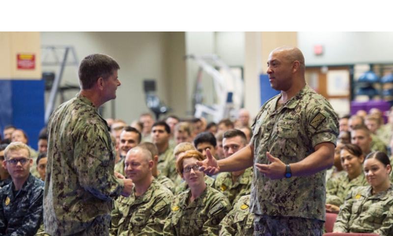 Petty Officer 1st Class Nicholas Perez, a culinary specialist working at Naval Support Activity Bahrain, right, asks Vice Adm. Bill Moran, Chief of Naval Personnel, about new changes to the Navy's body composition assessment during an all hands call Wednesday, Sept. 9, 2015.    Chris Church/Stars and Stripes