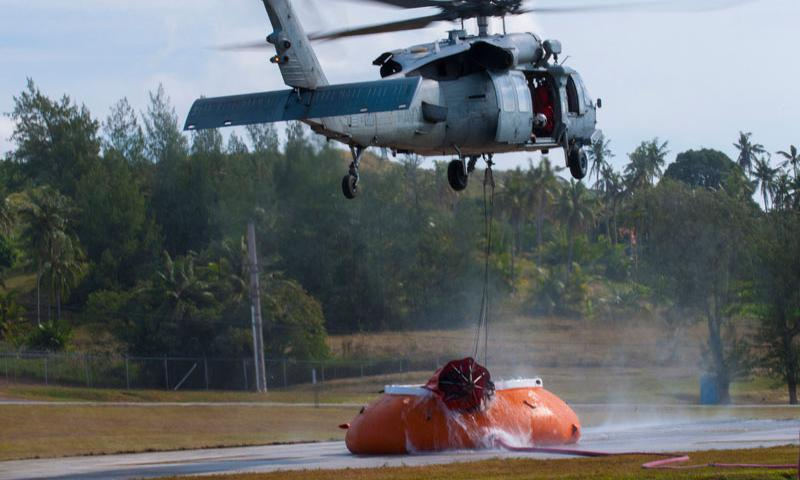 """SANTA RITA, Guam (Feb. 20, 2015) – A MH-60S Knighthawk with the """"Island Knights"""" of Helicopter Sea Combat Squadron (HSC)-25, hovers over a water """"pumpkin"""" to collect water from a """"Bambi Bucket"""" to conduct a """"Bambi Bucket Aerial Firefighting"""" training mission, as part of wildfire firefighting training missions performed Feb. 20 at the Naval Magazine, Naval Munitions Command, Naval Base Guam (NBG). (U.S. Navy photo by Jeff Landis)"""