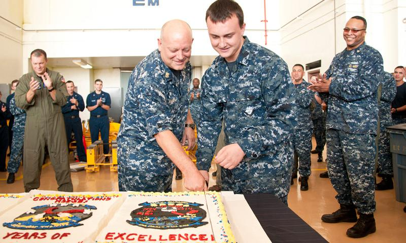 Helicopter Sea Combat Squadron (HSC) 25 Master Chief Aircraft Maintenanceman (AW) Micah Frazier, left, and Airman Recruit Connor Brown, the oldest and youngest Sailors of the command respectively, cut a ceremonial birthday cake for HSC-25 at the command headquarters on Andersen Air Force Base Feb. 7. HSC-25 celebrated 30 years of service and support to the island.