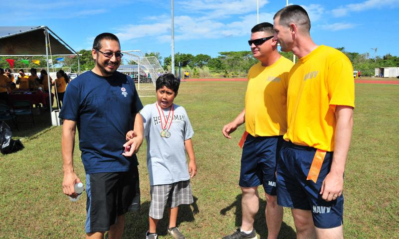 Construction Mechanic 2nd Class Jamie Allen, right, and Construction Mechanic 3rd Class (SCW) Michael Thompson, of Naval Mobile Construction Battalion 1, congratulate Joe Leon Guerrero and his son who competed in the static long jump during the 38th Annual Special Olympics Guam Track and Field event at Okkodo High School in Dededo April 12. Dozens of Sailors and airmen volunteered to coach and support hundreds of athletes with disabilities who competed in the event. (U.S. Navy photo by Leon Guerrero)
