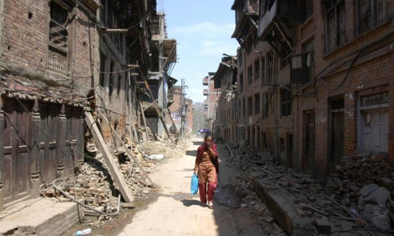 A woman walks past earthquake damaged buildings in Bhaktapur, Nepal, on Tuesday, May 5, 2015. The U.S. military will send 500 troops to Nepal in the near future as a follow-on force to the initial U.S. response to the April 25 earthquake.    Seth Robson/Stars and Stripes