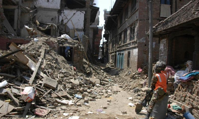 Soldiers watch debris fall from an earthquake-damaged building in Bhaktapur, Nepal, Tuesday, May 5, 2015.    Seth Robson/Stars and Stripes