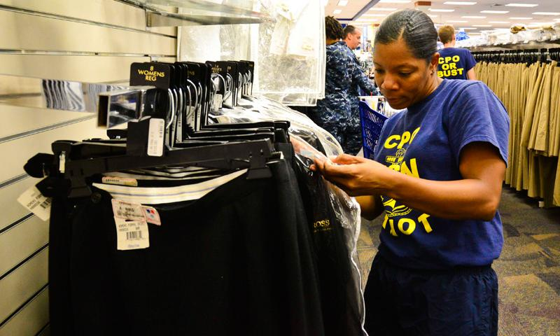 VIRGINIA BEACH, Va. (Aug. 28, 2014) Chief (select) Aviation Machinist's Mate Kizzy McBride, assigned to Strike Fighter Squadron (VFA) 34, looks for a dress blue jacket in her size at the Naval Air Station Oceana Navy Exchange (NEX) as part of uniform day. The annual event is a partnership between the Oceana NEX, commissary and uniform suppliers. (U.S. Navy photo by Mass Communication Specialist Seaman Kayla King)