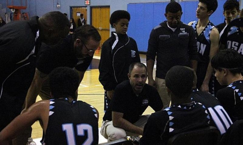 Osan boys coach Morgan Nugent chats it up with his charges during a timeout.    Jasmine V. Thomas/Special to Stars and Stripes
