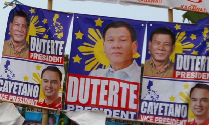 """A street corner in downtown Puerto Princesa, Philippines, is plastered with campaign posters. With Filipinos set to choose among five presidential candidates on May 9, 2016, Rodrigo Duterte, the candidate who said the U.S. """"should not meddle in our affairs,"""" holds a strong lead, according to the most recent poll released Sunday, April 24, 2016.     Wyatt Olson/Stars and Stripes"""