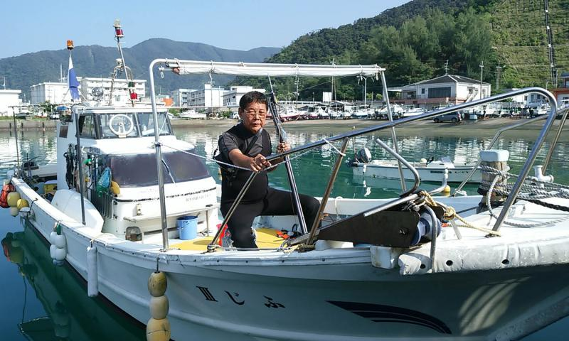 Fujio Sakoda, 80, seen here on his boat earlier this month, still fishes the waters near his Amami-Oshima island home where he spotted what is believed to be an American bomber from World War II. The bomber lies upside down in 150 feet of water. It is unknown if the pilot is still inside, but Sakoda hopes that the U.S. government will investigate. Courtesy of Ikuo Sakoda
