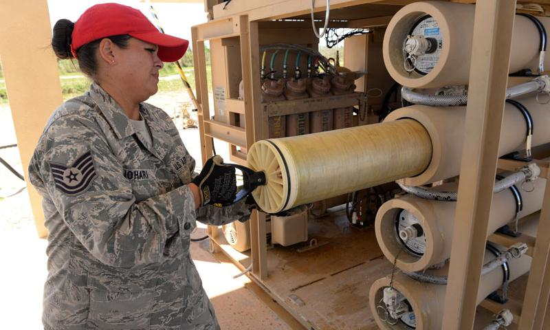 Tech. Sgt. Roshia Johari, 554th RED HORSE NCO in charge of water fuels systems maintenance contingency training, uses a element extraction tool to pull elements from their vessels on a Reverse Osmosis Water Purification Unit June 9, 2015, Andersen Air Force Base, Guam. At Andersen Air Force Base, Airmen are trained to be able to turn untested water into potable H2O using the ROWPU. (U.S. Air Force photo by Airman 1st Class Joshua Smoot)